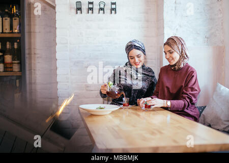 Deux musulmans caucasiens woman drinking tea in cafe Banque D'Images