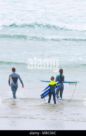 Un instructeur de surf et de jeunes surfeurs de marcher dans la mer. Banque D'Images