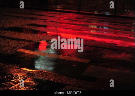 Néon rouge réflexions sur scène de rue à Paris. Et sombre soir de pluie en ville. Photo horizontale à l'exemplaire de l'espace. Passage pour piétons. Banque D'Images