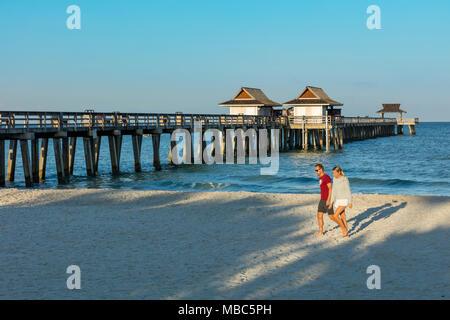 Couple en train de marcher le long de la plage tôt le matin à la jetée de Naples le long de la côte du golfe de la Floride, Naples, Florida, USA Banque D'Images