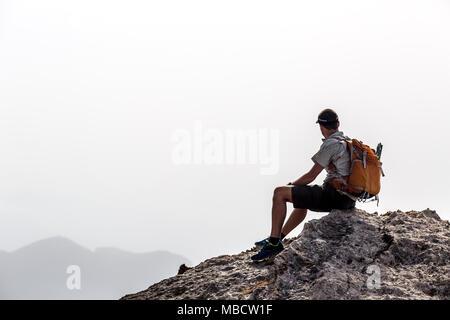 Randonnée homme silhouette dans les montagnes, d'inspiration et motivation concept. Sac à dos de randonneur avec le sommet de la montagne à la recherche de beaux paysages. Banque D'Images