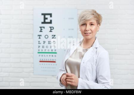Portrait de l'ophtalmologiste qualifié restant en face de la table d'inspection visuelle, la pendaison sur mur blanc en laboratoire médical. Médecin Expirienced peple aidant à améliorer leur santé oculaire et la vision. Banque D'Images