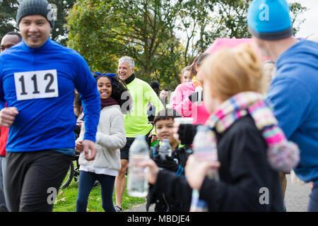 Les spectateurs de l'eau offrant aux coureurs de charity run dans park Banque D'Images