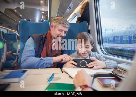 Père et fils à l'aide de smart phone sur le train de passagers