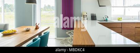 Comptoir blanc et violet à l'intérieur de chauffage cuisine moderne avec table à manger en bois