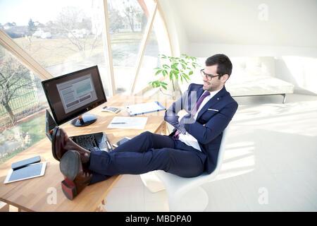 Longueur totale de shot of businessman wearing suit alors qu'il était assis à son bureau moderne avec ses jambes sur le bureau. Banque D'Images