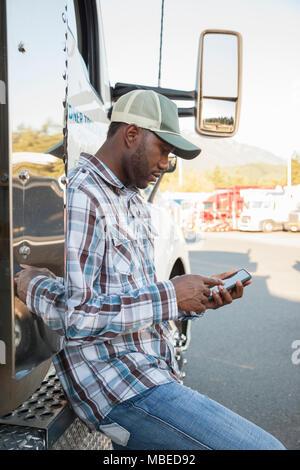 Black man truck driver texting tout en vous tenant à côté de la cabine de son camion stationné dans un lot à un arrêt de camion. Banque D'Images
