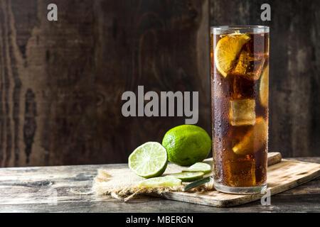 Cuba libre. Cocktail au rhum, citron vert et de la glace sur une table en bois. Banque D'Images