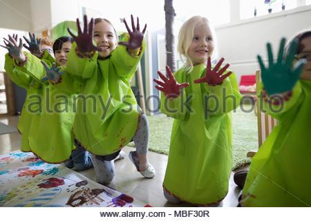 Les élèves de maternelle ludique en smocks montrant doigt peinture sur mains à l'affiche en classe Banque D'Images