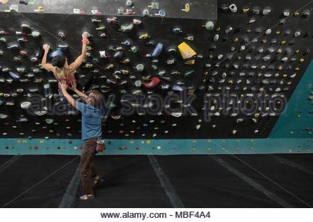Male rock climber spotting, soutenant female rock climber mur d'escalade à l'escalade Banque D'Images