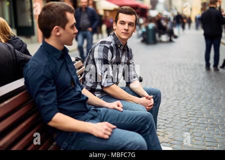 Deux homme s'asseoir sur le banc et parler sur la rue Banque D'Images