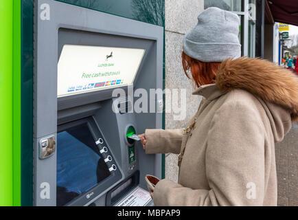 Senior woman prendre de l'argent à partir d'un GAB de la banque Lloyds en Angleterre, Royaume-Uni. Point trésorerie, distributeur, à l'aide d'un distributeur de billets, trou dans le mur. Le retrait d'argent.