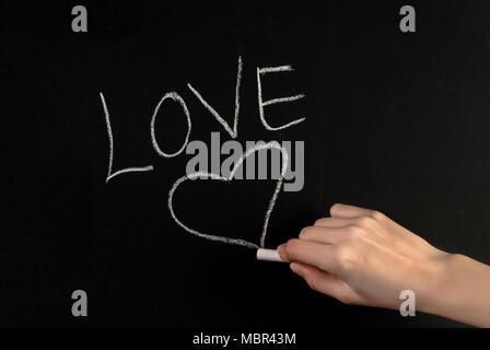 Fille main écrire mot amour et coeur dessin sur tableau noir avec craie blanche Banque D'Images
