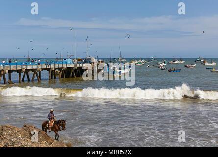 Sur la jetée de pêche pêcheurs Mancora de leurs bateaux et de superviser la distribution de leurs poissons, tandis qu'un cheval-cavalier rides le long de la plage dans la F