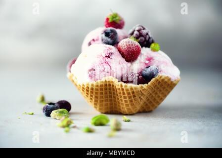 Glace à la rose aux fruits rouges, fraises, bleuets, framboises, pistaches dans waffle panier. Concept des aliments en été, l'espace de copie. Fruits sans gluten sains des glaces. Banner Banque D'Images