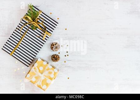 Vue de dessus de boîtes cadeau enveloppé en noir et blanc à rayures et parsemé d'or avec du papier et les cônes de pin sur un fond de bois blanc. Des cadeaux de Noël p Banque D'Images