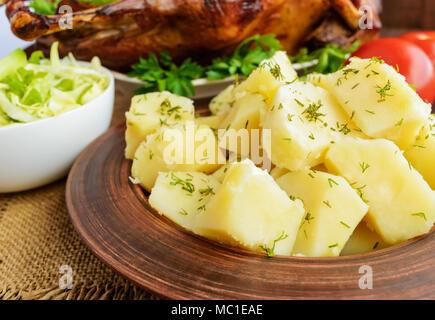 Des pommes de terre dans un bol d'argile cuite, salade de chou et d'oie. Banque D'Images