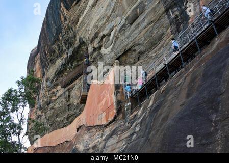 Vue horizontale de touristes sur la voie accrochée au flanc de la falaise à Sigiriya ou Lions Rock au Sri Lanka. Banque D'Images