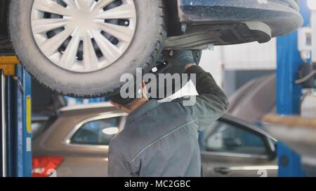 Mécanicien travaillant sur un service de pneus sur l'ascenseur dans une station-service Banque D'Images