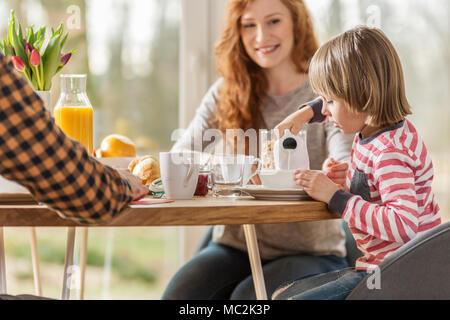 Garçon versant dans son bol de lait pendant le petit-déjeuner avec ses parents Banque D'Images