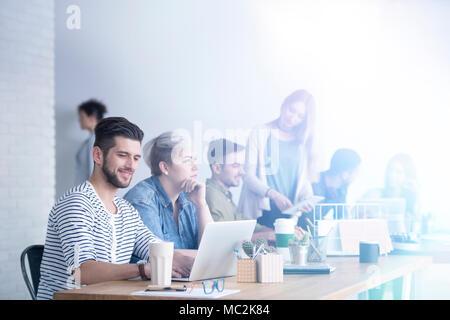 Groupe de personnes travaillant sur leur ordinateur portable dans un bureau d'une société internationale Banque D'Images