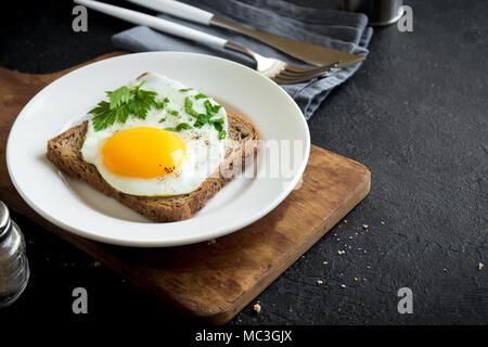 Œuf frit sur du pain grillé pour le petit-déjeuner. Œuf frit avec du pain et le persil sur plaque blanche sur noir, vue du dessus, copiez l'espace. Banque D'Images