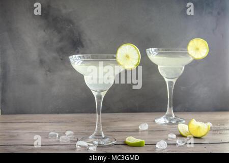 Marguerite Сocktail avec de la chaux et de la glace sur une table en bois, copie de l'espace. Cocktail Margarita classique.