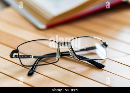 Livre ouvert et verres sur table en bois fermer Banque D'Images