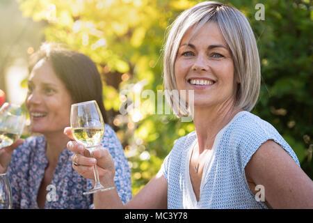 Groupe d'amis réunis autour d'une table dans un jardin pour passer un bon moment ensemble. Se concentrer sur une belle femme à la caméra à un verre à portée de main Banque D'Images