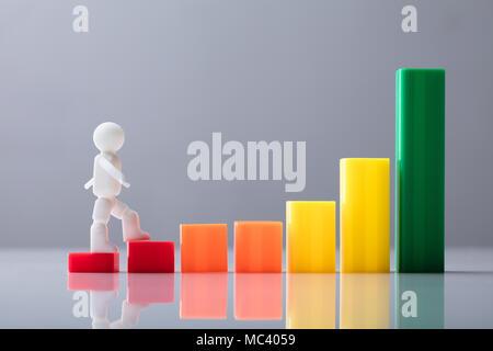 Figure humaine marcher sur l'augmentation de Multi Colored Business Graph en face de l'arrière-plan gris Banque D'Images