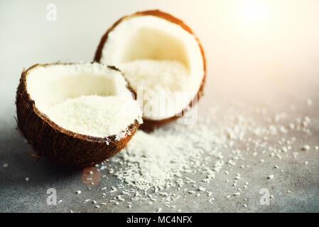 Les moitiés de noix de coco Coconut fuit avec copeaux sur fond de béton gris. Copyspace Banque D'Images