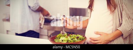 Pregnant woman mixing une salade dans la cuisine Banque D'Images