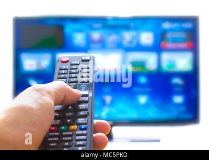 En appuyant sur la main sur la télécommande et change de chaîne pouce sur l'écran plat bleu Banque D'Images
