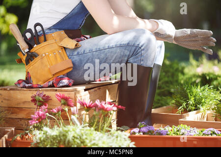 Femme en salopette et une ceinture à outils, assis sur une palette en bois et mettre des gants