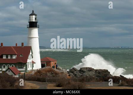 Les vagues déferlent sur les rochers géants par Portland Head Lighthouse et à Ram Island Ledge light comme soleil brise sotrm nuages dans le Maine. Banque D'Images