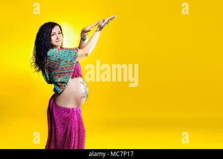 Enceinte happy woman in Indian sari avec tatouage au henné mehendi peint sur le ventre, le plaisir de jouer sur un fond jaune. Banque D'Images