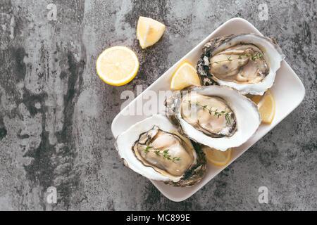 Des huîtres fraîches dans une assiette blanche avec glace et citron sur un bureau en bois Banque D'Images