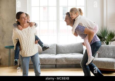 Les parents sur les enfants rire holding back donnant aux enfants piggyback ride jouer ensemble à la maison, en famille joyeux jeu drôle actifs ensemble, tr Banque D'Images