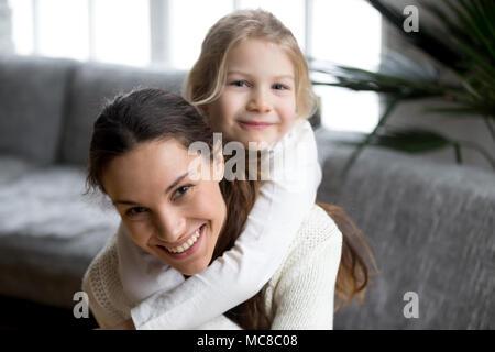 Heureux rire mère seule usurpation de petite fille à l'accueil souriant, maman et sa fille s'amuser jouant looking at camera, cute kid adopté sincère Banque D'Images