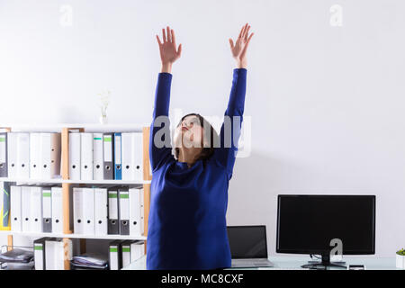 Young Businesswoman Doing Stretching Exercice in Office Banque D'Images