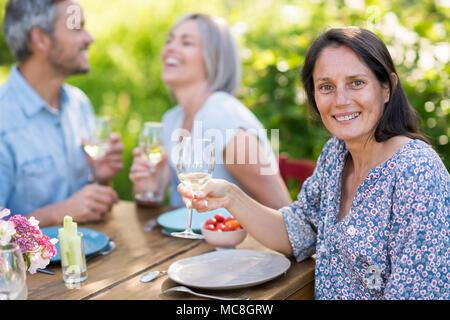 Un groupe d'amis se sont réunis pour partager un repas autour d'une table dans le jardin. Se concentrer sur une belle femme regardant la caméra Banque D'Images