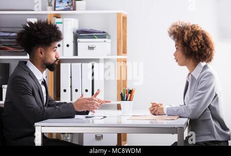 Vue latérale des deux jeunes Businesspeople Having Conversation in Office Banque D'Images
