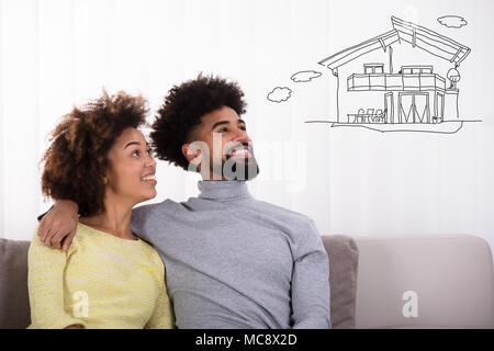 Heureux Couple Sitting on Sofa penser d'obtenir leur propre maison Banque D'Images