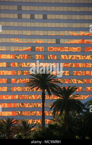 Vue extérieure d'un palmier silhouette devant une façade en verre moderne du casino à Las Vegas, NV, USA, au cours d'un beau coucher de soleil, panoramique Banque D'Images