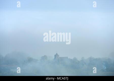 Firle, East Sussex. 14 avril 2018. L'église du village de Firle, East Sussex, émerge du brouillard matin basses couvrant le Low Weald par un beau matin de printemps. © Peter Cripps/Alamy Live News Banque D'Images