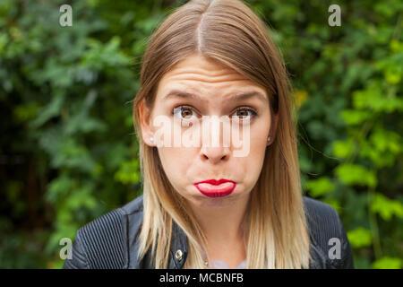 Jeune femme faisant une grimace à l'extérieur, fond vert. - Triste expression grincheux Banque D'Images