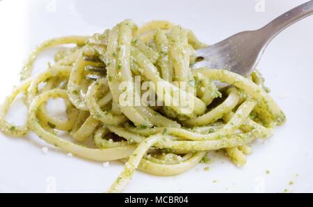 La nourriture italienne Spaghetti. Spaghetti avec sauce pesto fait maison et les feuilles de basilic sur la table avec la lumière du soleil, spaghetti avec sauce verte dans le