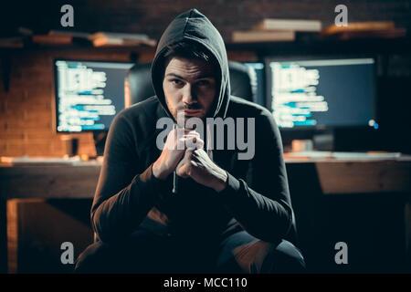 Portrait de jeune phoque à capuchon dangereux hacker dans black hoodie looking at camera posant avec code sur les écrans au fond, voler de l'information, la cybercriminalité se Banque D'Images