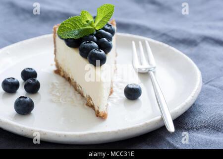 Tranche de gâteau au fromage avec des bleuets frais et feuille de menthe sur plaque blanche. Vue rapprochée Banque D'Images