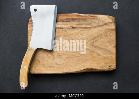 Ancien couperet à viande et planche à découper sur fond sombre, vue supérieure avec copie espace pour le texte Banque D'Images